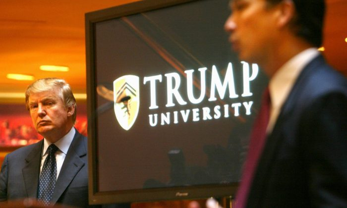 Real estate mogul and TV star Donald Trump (L) listens as Michael Sexton introduces him to announce the establishment of Trump University during a news conference in New York on May 23, 2005. (AP Photo/Bebeto Matthews)