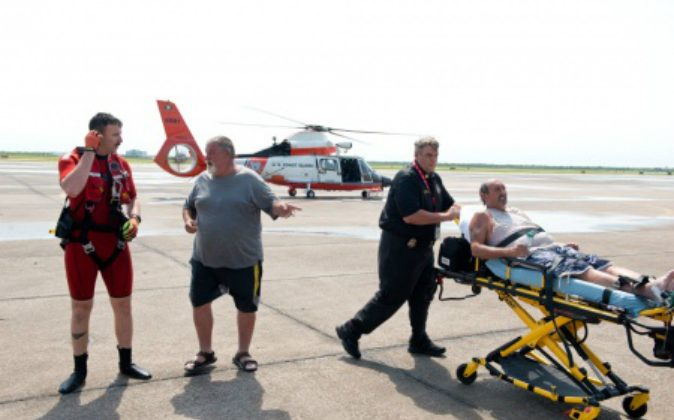 Petty Officer 2nd Class Jesse Weaver and survivor Michael Watkins speak as survivor Raymond Jacik is wheeled away by EMS after having been missing for more than two days in Galveston Bay, April 27, 2016. The two men were reported missing Tuesday morning after they didn't return home Monday afternoon becuase their boat had capsized in Trinity Bay. U.S. Coast Guard (photo by Petty Officer 3rd Class Dustin R. Williams)