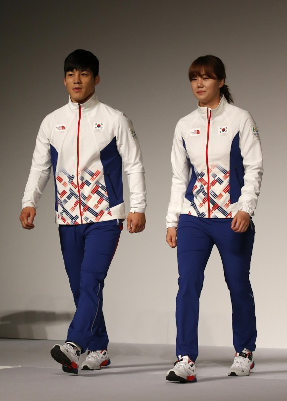 South Korean Olympic wrestling athlete Kim Hyeon-woo, left, and handball athlete Kim On-a, right, present the South Korean Olympic team uniforms for the medal ceremony of the 2016 Rio de Janeiro Olympic Games at Korean National Training Center in Seoul, South Korea, Wednesday, April 27, 2016. (AP Photo/Lee Jin-man)
