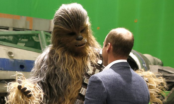 Britain's Prince William, talks with  the Star Wars character Chewbacca during a tour of the Star Wars sets at Pinewood studios in Iver Heath, west of London on Tuesday April 19, 2016. Prince William and Prince Harry  toured Pinewood to visit the production workshops and meet the creative teams working behind the scenes on the Star Wars films. (Adrian Dennis, Pool via AP)