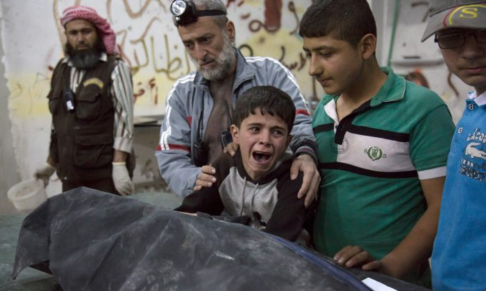 A Syrian boy is comforted as he cries next to the body of a relative who died in a reported airstrike on April 27 in the rebel-held neighbourhood of al-Soukour in the northern city of Aleppo. (Karam Al-Masri/AFP/Getty Images)