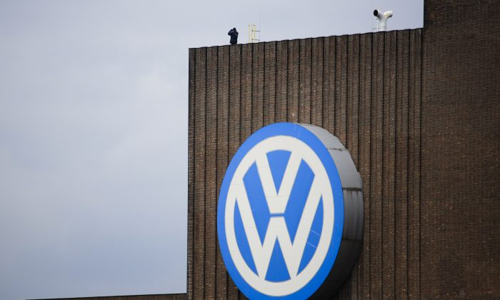 A security guard stands on the roof of the Volkswagen old power plant and monitors the area during the company's annual press conference in Wolfsburg, Germany, Thursday, April 28, 2016. (AP Photo/Markus Schreiber)