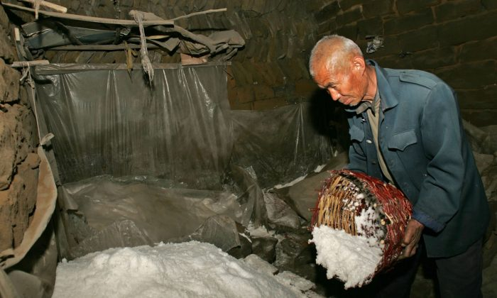 A Chinese farmer pours salt onto a heap at Lijiawa Village in Zizhou County, Shaanxi Province, China, on March 31, 2006. (China Photos/Getty Images)