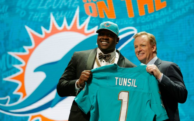 Laremy Tunsil of Ole Miss holds up a jersey with NFL Commissioner Roger Goodell after being picked #13 overall by the Miami Dolphins during the first round of the 2016 NFL Draft at the Auditorium Theatre of Roosevelt University on April 28, 2016 in Chicago, Illinois. (Photo by Jon Durr/Getty Images)