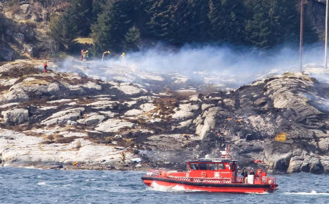 A search and rescue vessel patrols off the island of Turoey, near Bergen, Norway, as emergency workers attend the scene of a helicopter crash believed to have 13 people aboard, Friday April 29, 2016.  The helicopter carrying around 13 people from an offshore oil field crashed Friday near the western Norwegian city of Bergen, police said. Many are feared dead.  (Rune Nielsen/NTB scanpix via AP)