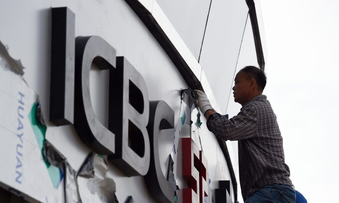 A worker installs sign outside a branch of the Industrial and Commercial Bank of China (ICBC) in Beijing.   (Greg Baker/AFP/Getty Images)