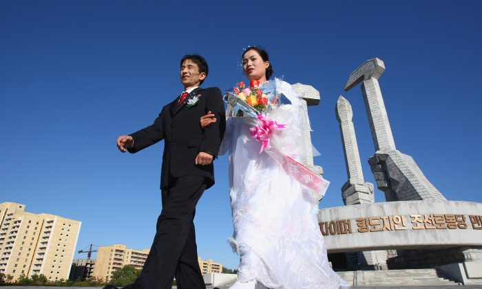 Hu Kwang Rim and his wife Hwang Ju Ok celebrate their wedding at the Monument of Party's foundation of DPR Korea in Pyongyang, North Korea, on Oct. 19, 2007. (Alexander Hassenstein/Getty Images)