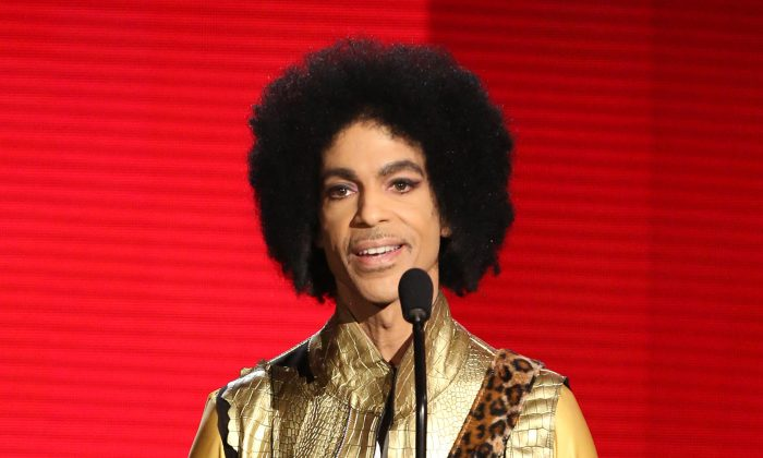 """FILE - In this Nov. 22, 2015 file photo, Prince presents the award for favorite album - soul/R&B at the American Music Awards in Los Angeles. A famous bassist and longtime friend of pop megastar Prince says the artist found """"real happiness"""" in his faith and could stay up all night talking about the Bible. Larry Graham tells The Associated Press that Prince became a Jehovah's Witness later in life and that it changed the star's music and lifestyle. (Photo by Matt Sayles/Invision/AP, File)"""