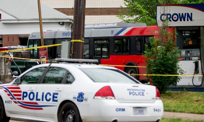 Police work at a crime scene after authorities say a man attacked a bus driver, stole the bus, then struck and killed a man after the bus jumped a curb at a gas station at the corner of Helen Burroughs Avenue and Minnesota Avenue in Northeast Washington, Tuesday, May 3, 2016. (AP Photo/Andrew Harnik)