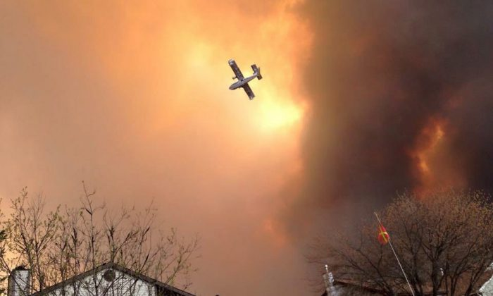 Smoke fills the air as a small plane flies overhead in Fort McMurray, Alberta, Tuesday, May 3, 2016. The entire population of the Canadian oil sands city of Fort McMurray, has been ordered to evacuate as a wildfire whipped by winds engulfed homes and sent ash raining down on residents. (Kitty Cochrane/The Canadian Press via AP)
