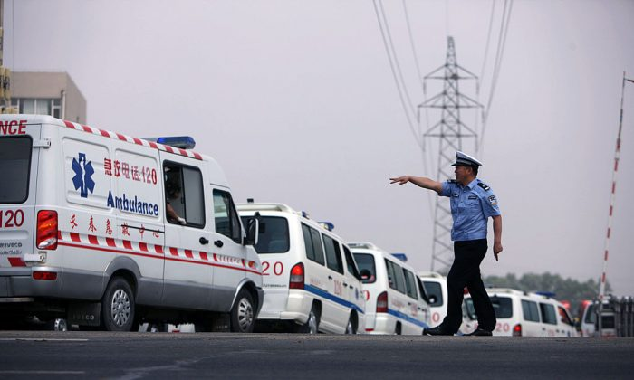 A police officer waves to an ambulance in Dehui, China's Jilin Province, on June 3, 2013. Rogue operators of unofficial ambulances have become a big problem in China. (STR/AFP/Getty Images)