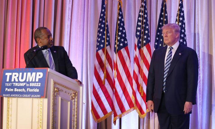 Former Republican presidential candidate Ben Carson looks back at Republican presidential candidate Donald Trump as he give him his endorsement at the Mar-A-Lago Club on March 11, 2016 in Palm Beach, Florida. (Photo by Joe Raedle/Getty Images)