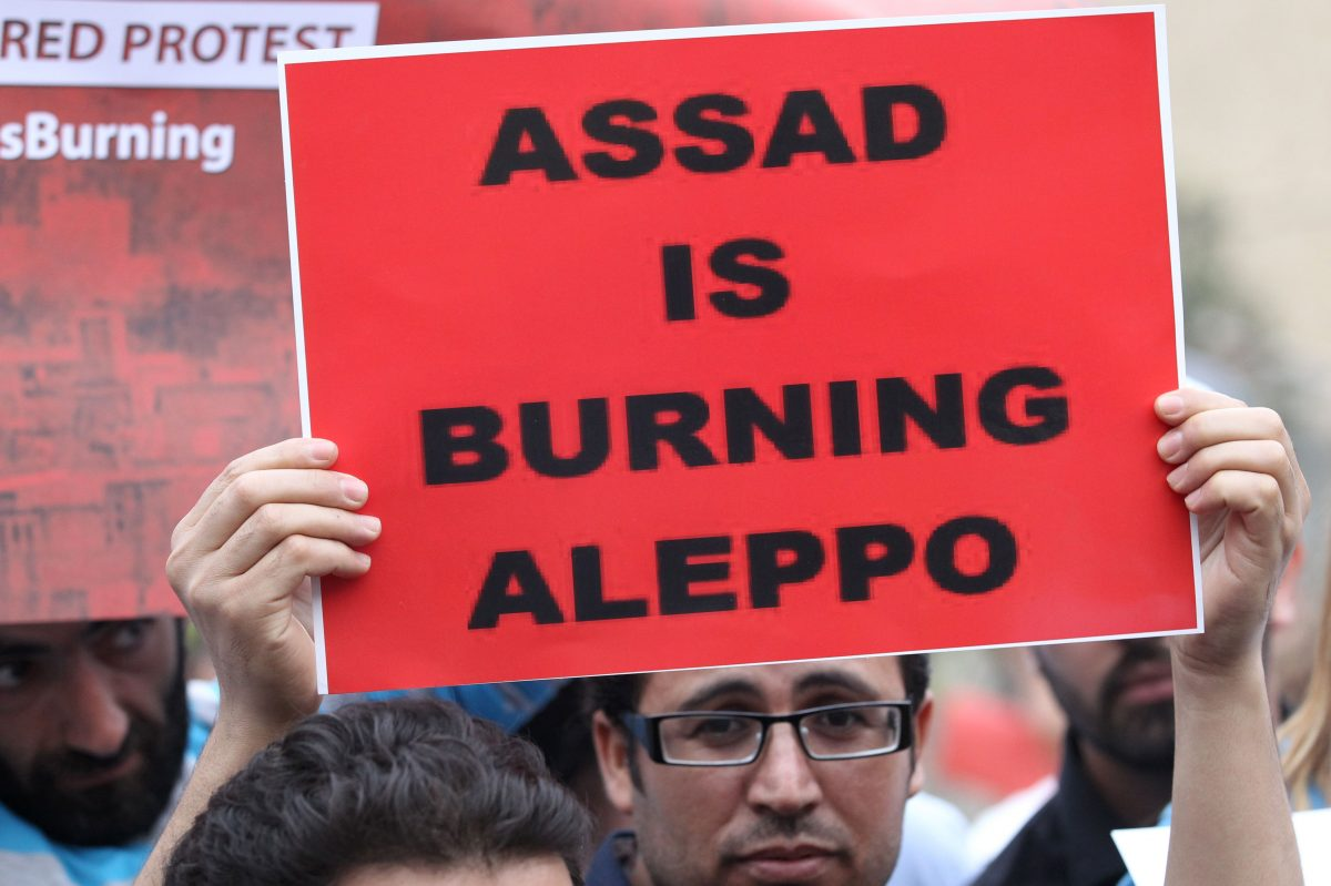 A protester holds a banner as he takes part in a demonstration in front of U.N. offices in Beirut in solidarity with the civilians of the northern Syrian city of Aleppo and against the regime of the Syrian President Bashar Assad, on May 1, 2016. (Anwar Amro/AFP/Getty Images)