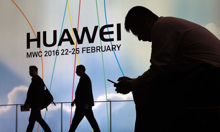 A man uses a mobile phone next to the stand of Chinese telecoms firm Huawei at the Mobile World Congress in Barcelona, Spain on Feb. 22, 2016. (Lluis Gene/AFP/Getty Images)