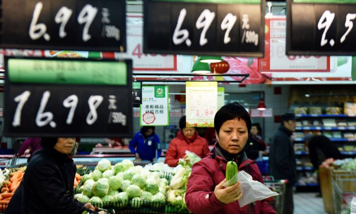 A customer selects vegetables at a supermarket in Hangzhou, in eastern China's Zhejiang province on March 10, 2016. (STR/AFP/Getty Images)