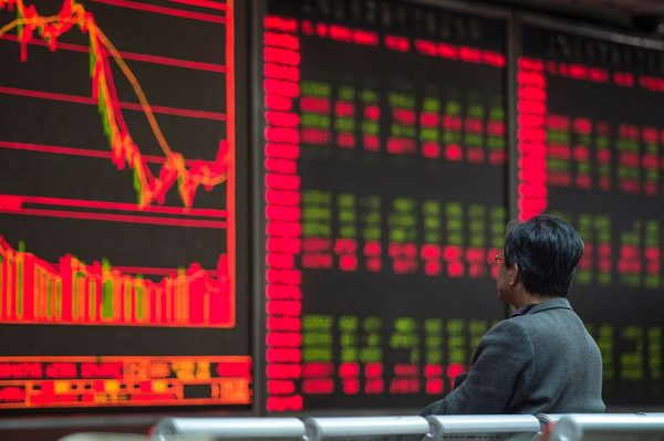 An investor watches stock prices on screens at a securities company in Beijing on March 22, 2016. (Fred Dufour/AFP/Getty Images)