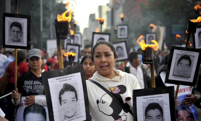 The parents of 43 missing students from the Ayotzinapa Teachers' College hold their portraits and torches during a march 18 months after their disappearance in Mexico City on April 26, 2016. (Yuri Cortez/AFP/Getty Images)