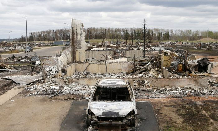 A charred vehicle and home are pictured in the Beacon Hill neighbourhood of Fort McMurray, Alberta, Canada, May 9, 2016 after wildfires forced the evacuation of the town. (Chris Wattie/AFP/Getty Images)