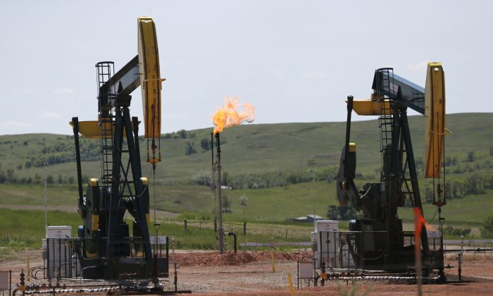 In this June 12, 2014 file photo, oil pumps and natural gas burn off in Watford City, N.D. (AP Photo/Charles Rex Arbogast)
