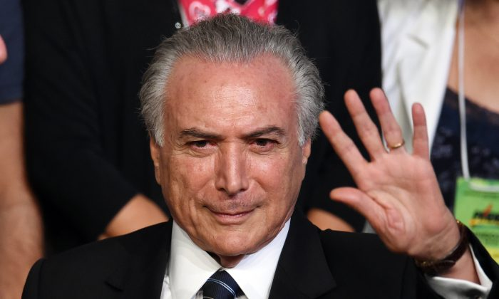 Brazilian Vice President Michel Temer waves during the Brazilian Democratic Movement Party (PMDB) national convention in Brasilia, on March 12, 2016. (Evaristo Sa/AFP/Getty Images)