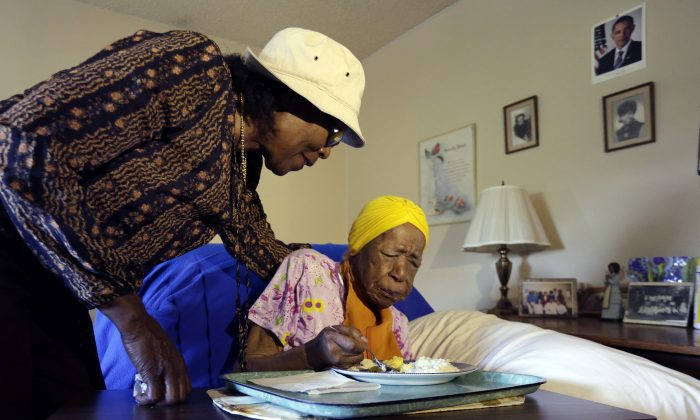 FILE - In this Monday, June 22, 2015 photo, Lois Judge, left, helps her aunt Susannah Mushatt Jones, during breakfast in Jones' room at the Vandalia Avenue Houses, in the Brooklyn borough of New York. Jones, the world's oldest person, has died in New York at age 116. Robert Young, a senior consultant for the Gerontology Research Group, says Jones died at a senior home in Brooklyn Thursday night, May 12, 2016. He said she had been ill for the past 10 days. (AP Photo/Richard Drew, File)