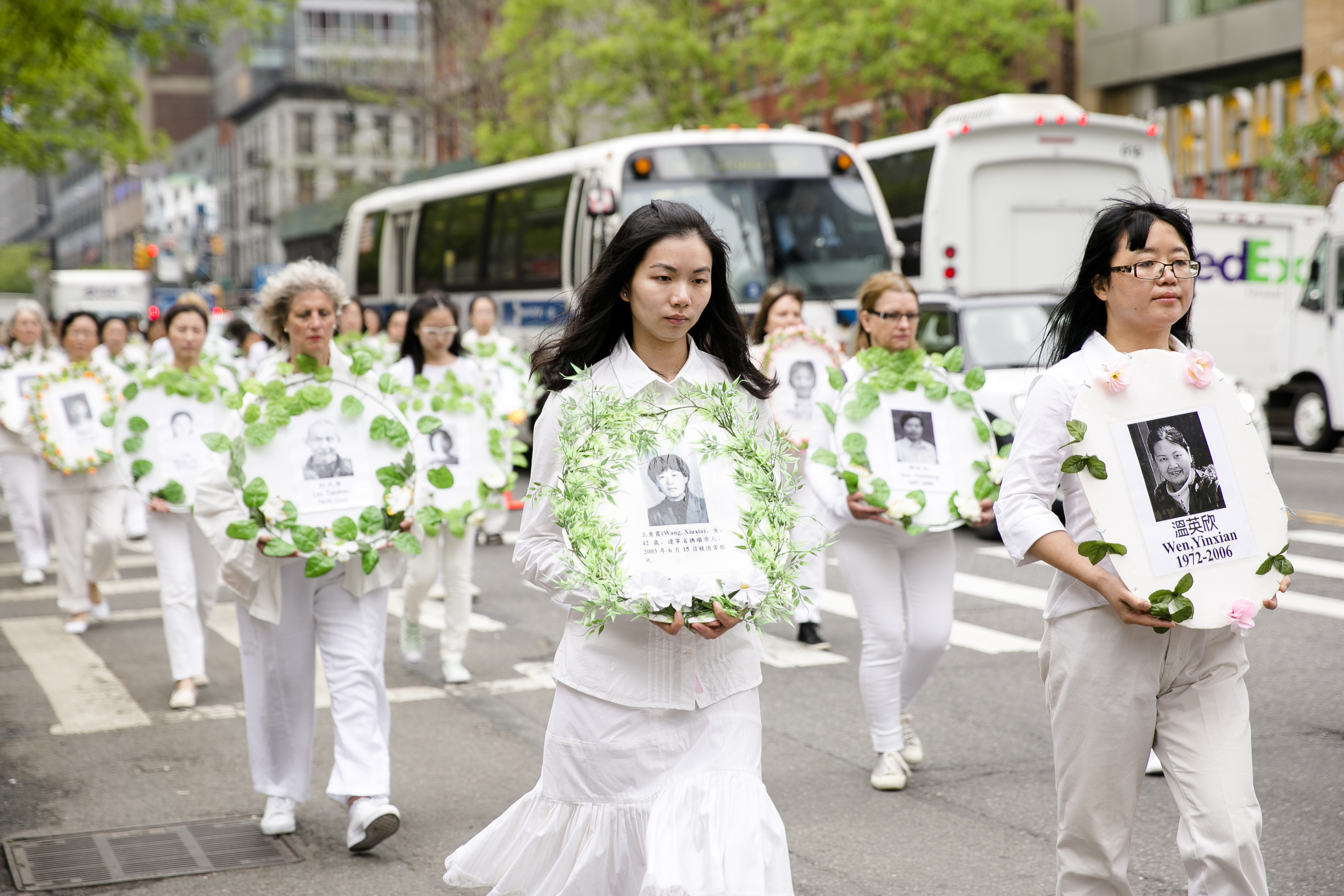 Falun Gong practitioners hold portraits of those killed in the persecution in China during the World Falun Dafa Day parade along 42nd Street in New York, on May 13, 2016. (Samira Bouaou/Epoch Times)