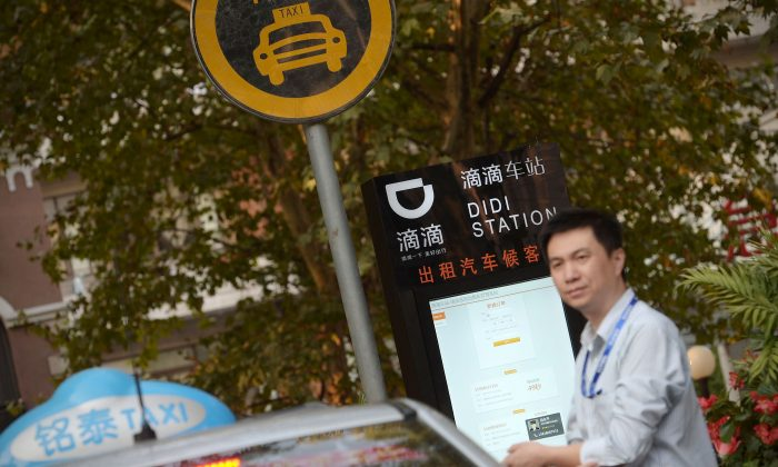 A taxi driver waits at a Didi Station, a road-side stop for taxis booked by the Chinese car-hailing app Didi Chuxing in Shanghai. (Chinatopix via AP)