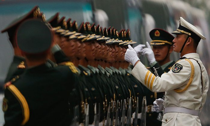 Chinese soldiers stand for inspection during a welcoming ceremony for Venezuela President Nicolas Maduro Moros in Beijing on September 22, 2013. The Chinese regime has started dismantling business ventures run by its military. (Lintao Zhang/Getty Images)
