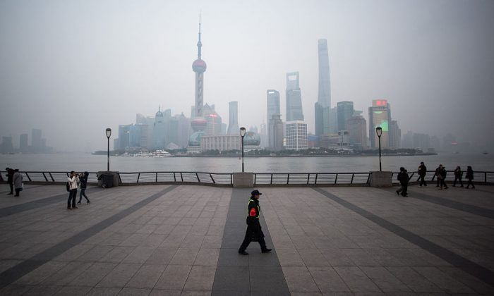 A security guard walks at the bund near the Huangpu river across the Pudong New Financial district, in Shanghai on January 18, 2016. (Johannes Eisle/AFP/Getty Images)