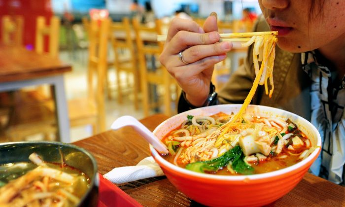 A woman lunches on a bowl of soup noodles at a food court in Beijing on April 6, 2011. (Frederic J. Brown/AFP/Getty Images)
