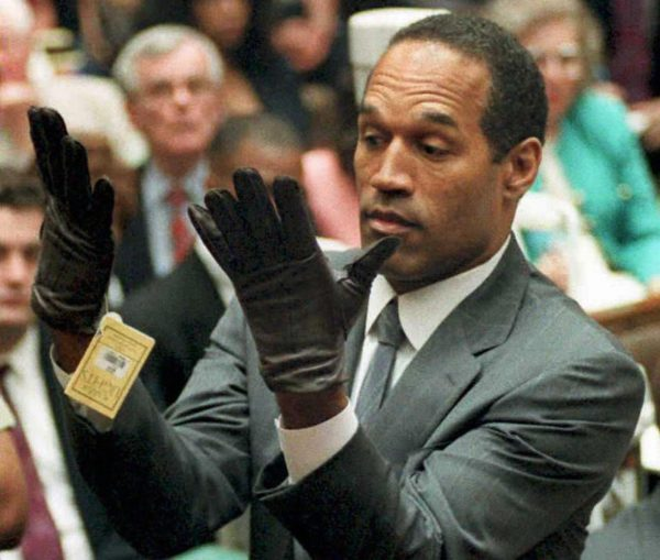 This 21 June 1995 file photo shows former US football player and actor O.J. Simpson looking at a new pair of Aris extra-large gloves that prosecutors had him put on during his double-murder trial in Los Angeles. (Vince Bucci/AFP/Getty Images)