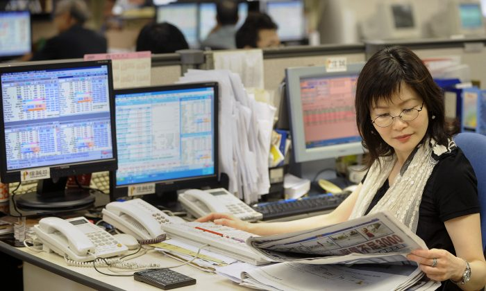 A trader reads a newspaper at a local brokerage in Hong Kong on May 5, 2009. (MIKE CLARKE/AFP/Getty Images)