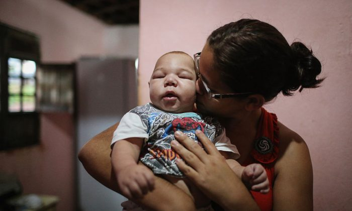 David Henrique Ferreira, 5 months, who was born with microcephaly, is kissed by his mother Mylene Helena Ferreira on January 29, 2016 in Recife, Pernambuco state, Brazil. (Mario Tama/Getty Images)