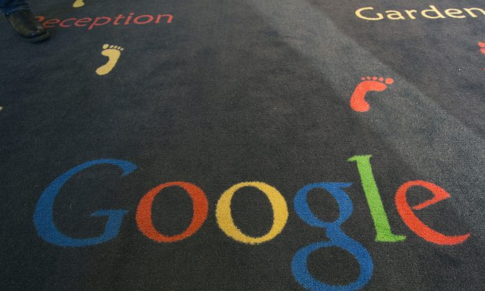 "FILE -  This Tuesday, Dec. 10, 2013 file photo shows the Google logo printed on a carpet during the inauguration of the new Google cultural institute in Paris, France. French police have raided Google's Paris offices as part of an investigation into ""aggravated tax fraud"" and money laundering, authorities said Tuesday. (AP Photo/Jacques Brinon, File)"