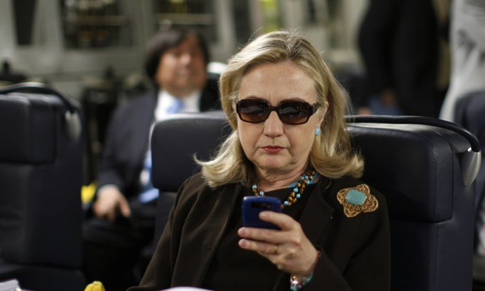 Hillary Rodham Clinton checks her Blackberry from a desk inside a C-17 military plane upon her departure from Malta, in the Mediterranean Sea, bound for Tripoli, Libya.(AP Photo/Kevin Lamarque, Pool)