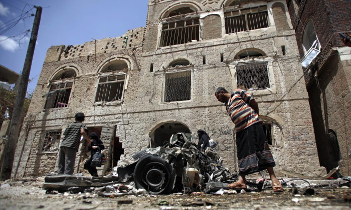FILE - In this Tuesday, June 30, 2015 file photo, People stand amid wreckage of a vehicle at the site of a car bomb attack near a military hospital in Sanaa, Yemen. The World Health Organization says nearly 1,000 people have been killed worldwide in attacks on medical facilities in conflicts over the past two years in violation of humanitarian norms. (AP Photo/Hani Mohammed)
