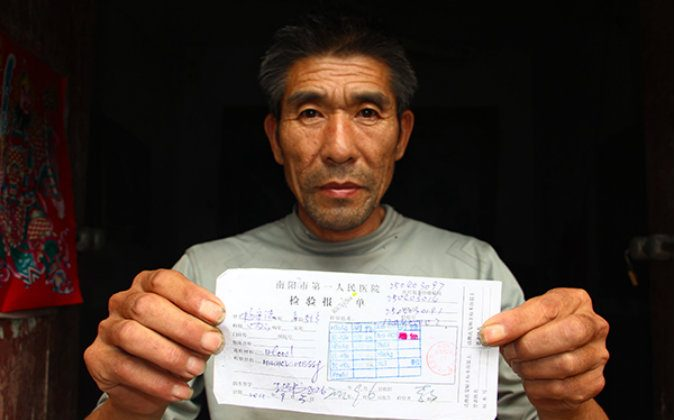 Yang Shoufa holds the corrected diagnosis of his AIDS. (via The Paper)