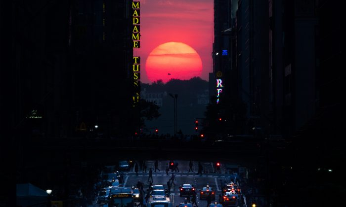 """The sun sets along 42nd Street in Manhattan during an annual phenomenon known as """"Manhattanhenge,"""" when the sun aligns perfectly with the city's transit grod, Wednesday, May 29, 2013, in New York. (AP Photo/John Minchillo)"""