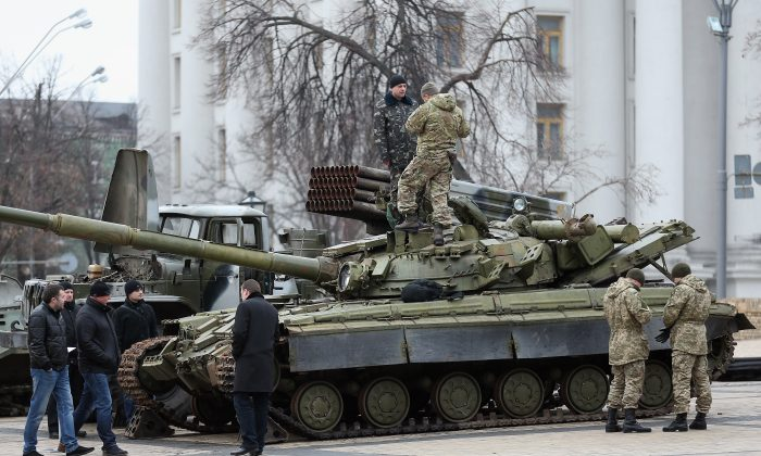 """Security forces inspect a heavy tank and a rocket launcher truck on Feb. 22, 2015, in Kiev, Ukraine, in an exhibition the Ukrainian government says demonstrates Russian involvement in recent conflicts. A new report from RAND Corporation says Russia, China, and Iran are using """"short of war"""" methods in modern conflicts. (Sean Gallup/Getty Images)"""