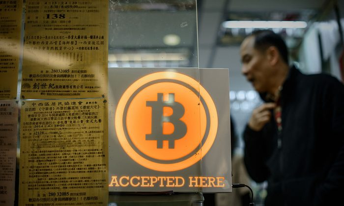 A man walks out of a shop displaying a bitcoin sign during the opening ceremony of the first bitcoin retail shop in Hong Kong on February 28, 2014. (PHILIPPE LOPEZ/AFP/Getty Images)