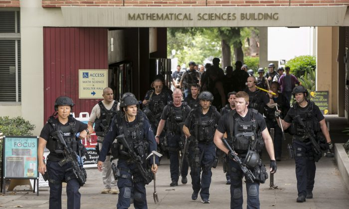 Los Angeles Police officers walk by the Mathematical Sciences Building on the UCLA campus after a fatal shooting at the University of California, Los Angeles, Wednesday, June 1, 2016, in Los Angeles. (AP Photo/Damian Dovarganes)