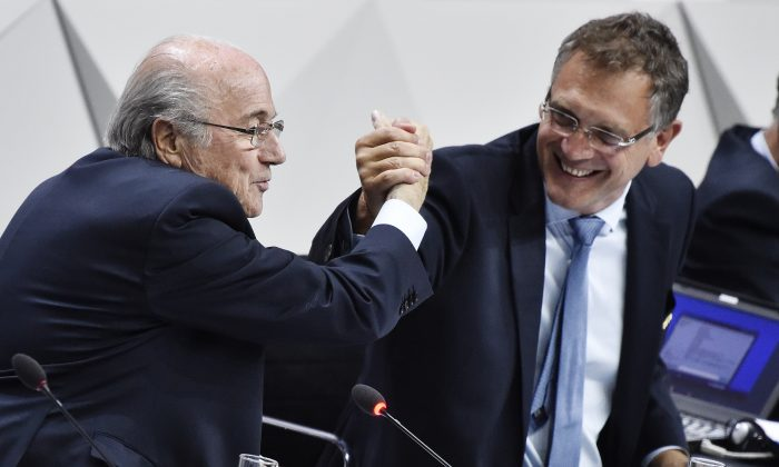 FIFA President Sepp Blatter (L) makes a symbolic handshake with FIFA general secretary Jerome Valcke during the 65th FIFA Congress in Zurich on May 29, 2015. (Michael Buholzer/AFP/Getty Images)