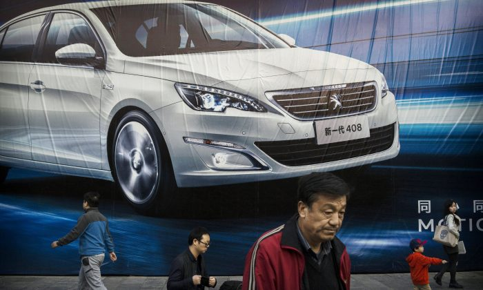 Chinese walk past an advertisement for a foreign auto maker on a wall on Oct. 27, 2014 in Beijing, China. The Chinese leaders economic reform plan face several structural obstacles. (Kevin Frayer/Getty Images)