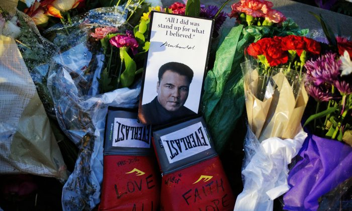 Boxing gloves and a message sit among flowers at a makeshift memorial to Muhammad Ali at the Muhammad Ali Center in Louisville, Ky., on June 4, 2016. Muhammad Ali died Friday, June 3, at age 74. (AP Photo/David Goldman)