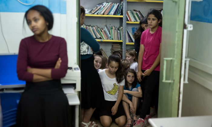 Israeli schoolchildren gather in a bomb shelter at a school in Jerusalem after sirens sounded across Israel as part of country-wide massive civil defence exercise aimed at preparing the country for air or missile attacks involving non-conventional weapons on June 2, 2015. (Photo credit should read MENAHEM KAHANA/AFP/Getty Images)