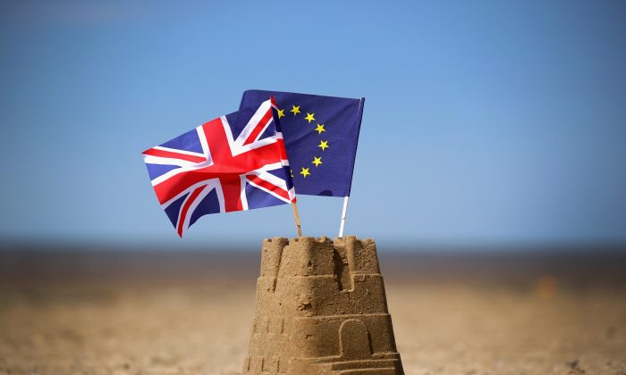 The flags of the European Union and the United Kingdom on top of a sand castle on a beach in Southport, U.K., on May 9, 2016. (Christopher Furlong/Getty Images)