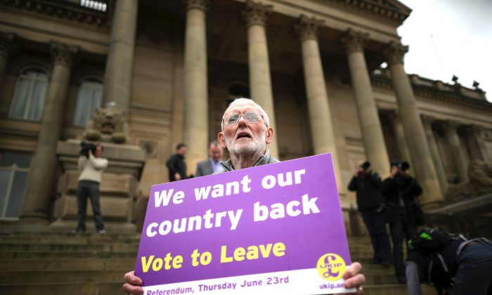 """A """"Vote to Leave"""" campaigner holds a placard as Leader of the United Kingdom Independence Party (UKIP), Nigel Farage, campaigns for votes to leave the European Union in the June 23rd referendum in Bolton, England, on May 25, 2016. (Christopher Furlong/Getty Images)"""