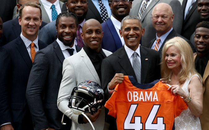 U.S. President Barack Obama holds up a Denver Broncos jersey presented to him as a gift by Annabel Bowlen (R), wife of Broncos majority owner Pat Bowlen, while welcoming the National Football League Super Bowl champion Denver Broncos to the White House Rose Garden on June 6, 2016 in Washington, DC. (Win McNamee/Getty Images)