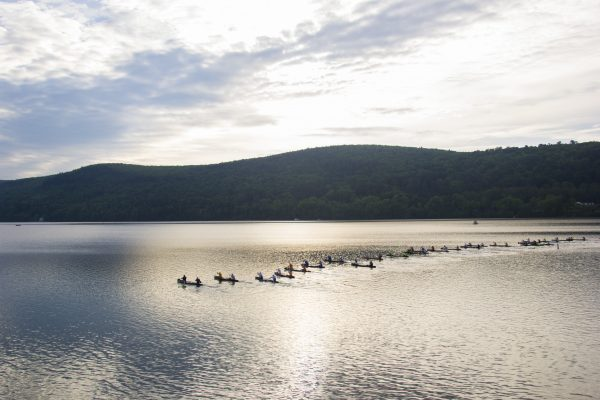 A canoe race takes place on the Otsego Lake. In the early morning hours, the lake shimmers like antique silver. (Channaly Philipp/Epoch Times)