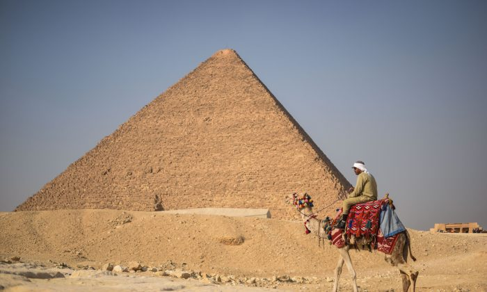 An Egyptian man rides a camel in front of one the Giza pyramids in the southern Cairo Giza district on Jan. 20, 2016. (Mohamed El-Shahed/AFP/Getty Images)